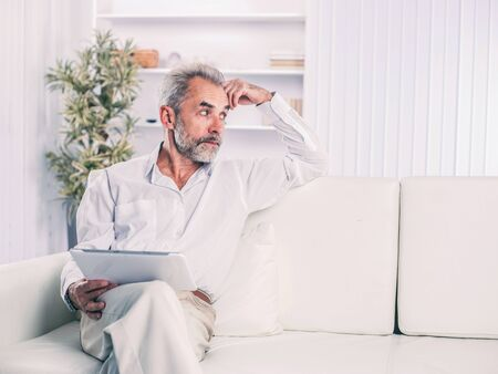 confident businessman with digital tablet sitting on sofa in bright office