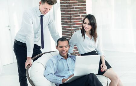successful businessman with his assistants in a discussion of the information from the laptop. Stok Fotoğraf