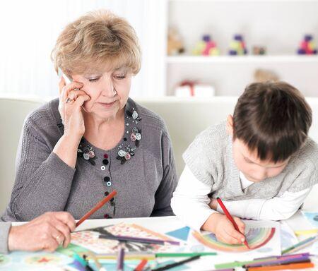Moderne Großeltern besuchen Enkel am Tisch im Kinderzimmer sitzen.