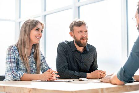Arbeitgeber spricht mit Mitarbeitern bei einer Besprechung im Büro. Standard-Bild