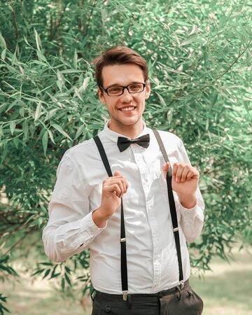 happy groom straightening his bow tie in front of camera