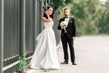 bride and groom standing on a city street.