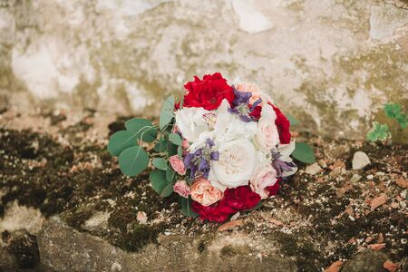 wedding bouquet of the bride on a stone wall background