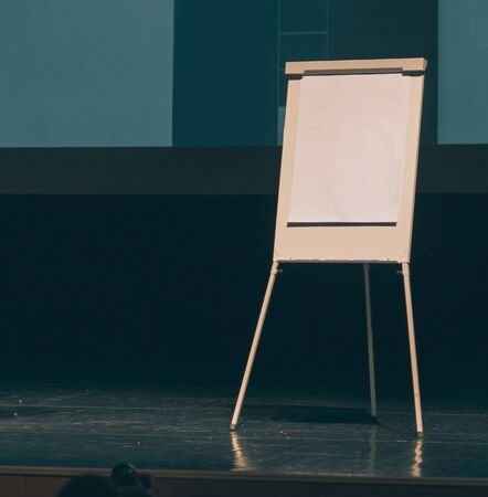 flipchart in front of a white screen on the stage of the conference room Stock fotó