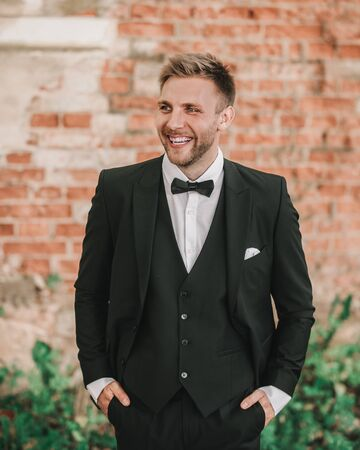 portrait of a happy groom on the background of old brick wal