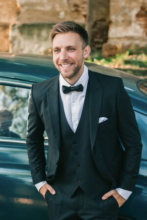 close up. the proud groom standing near the car the car