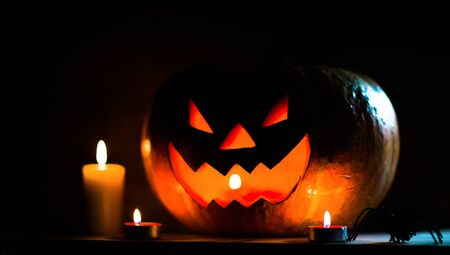 candles, pumpkin and spider on a wooden table Imagens