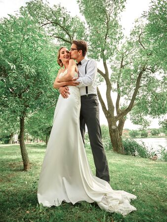 in full growth. newlyweds hugging in spring Park Stock Photo