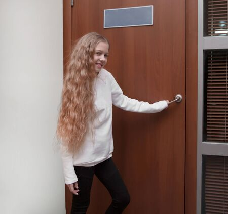 schoolgirl opening the door to the principals office Stock Photo