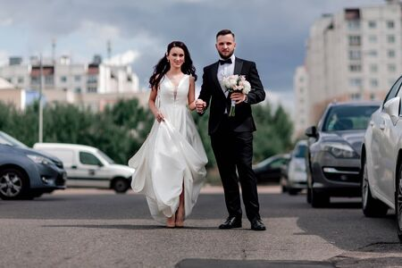happy bride and groom walking down the street in the big city