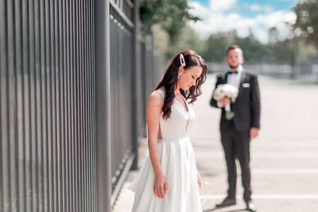 happy bride in wedding dress standing on city street Stock Photo