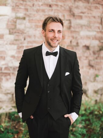 e smiling groom in the background of old brick wall. Stock Photo
