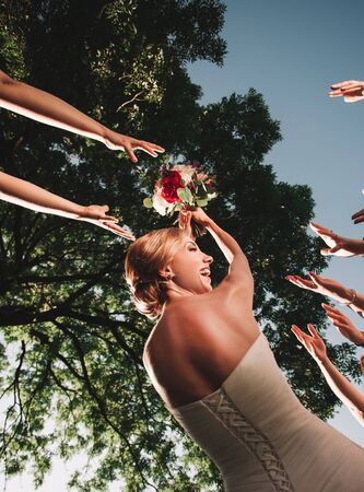 smiling bride throws the wedding bouquet of her friends Stock Photo