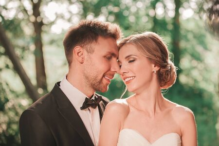 portrait of happy bride and groom in summer Park.