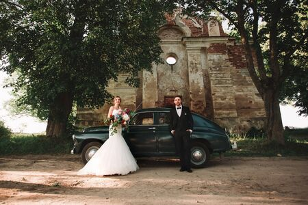 happy newlyweds standing next to a stylish car during the walk