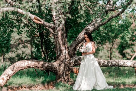 grooms bride standing near the old big tree