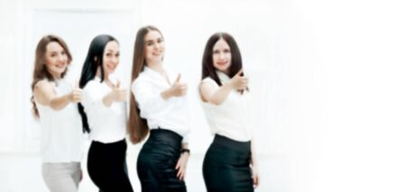blurred image for the advertising text. photo with copy space. triumphant business team holding thumbs up.