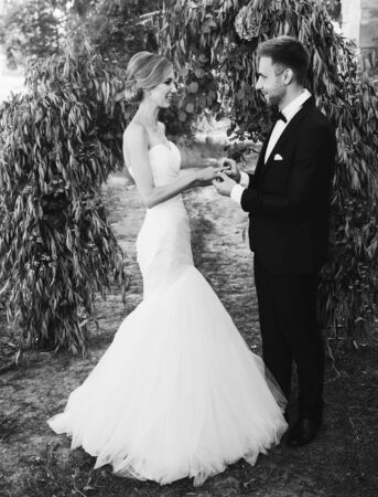 couple in a wedding dress exchanges rings in the garden with an arch. black and white photo Stock Photo