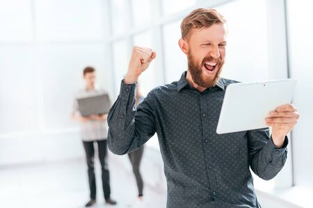 happy man with digital tablet standing in office lobby Stok Fotoğraf