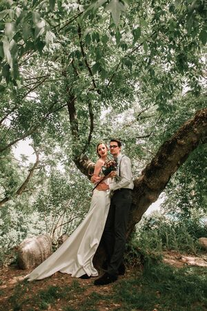 happy bride and groom standing near the tree . Stock Photo