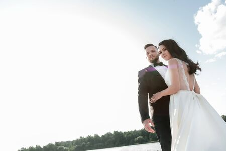 portrait of happy bride and groom against the summer sky
