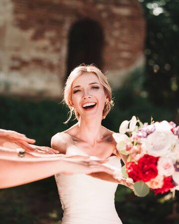 sweet bride passing wedding bouquet in the hands of her friends.