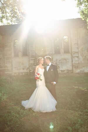 couples of newlyweds standing near the old manor in the evening