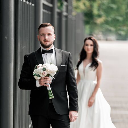 groom with a bouquet of flowers waiting for his bride on the city street