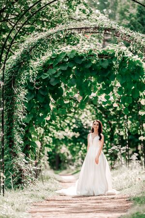 portrait of a happy bride standing under an arch in the Park