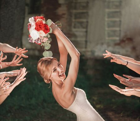 beautiful bride throws wedding bouquet to her friends