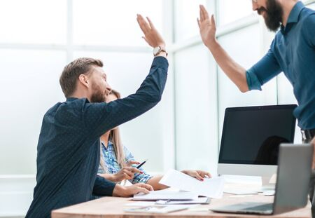 satisfied employees giving each other a high five at the workplace in the office