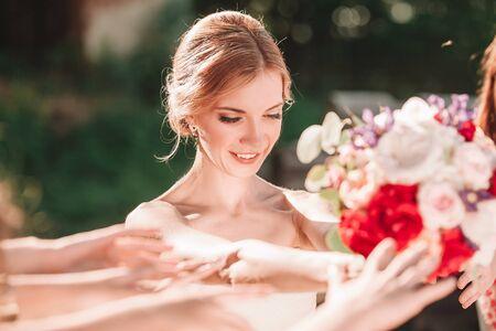 smiling bride handing wedding bouquet to her friends.