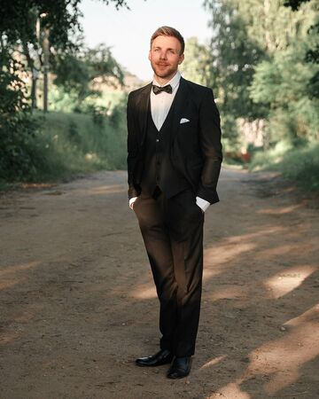 groom in a wedding suit on the background of nature.
