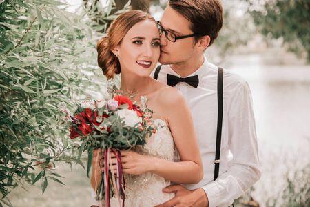 happy groom kissing his bride in city Park
