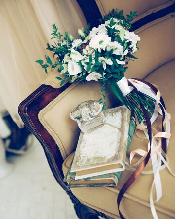 close up. bouquet and perfume bottle on vintage sofa. Stock Photo
