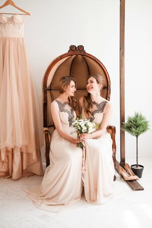 bridesmaid with a wedding bouquet sitting in a vintage chair.