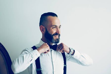 close up. smiling man straightening his bow tie