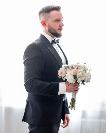 groom with wedding bouquet waiting for his bride