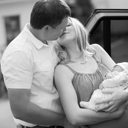 happy husband kissing his wife with a newborn baby Stock fotó