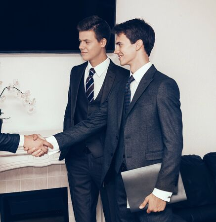 business partners shaking hands in the meeting room