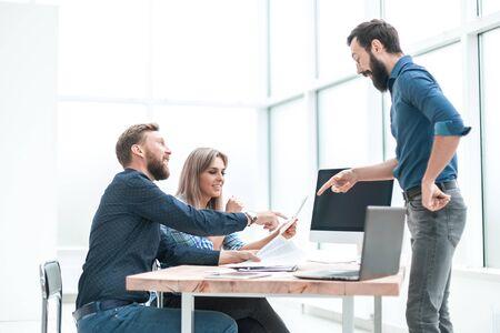 Grupo de gente de negocios discutiendo algo cerca del escritorio de la oficina. Foto de archivo