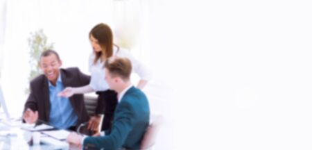 blurred image for the advertising text. photo with copy space. smiling business team talking ,sitting at their Desk