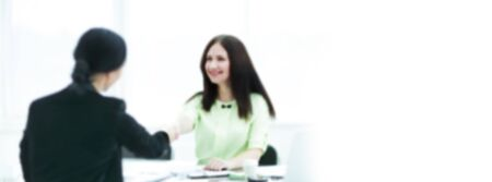 blurred image for the advertising text. photo with copy space. welcome handshake of two business women at the Desk. Reklamní fotografie