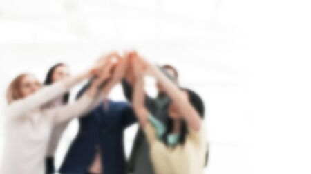 blurred image for the advertising text. photo with copy space. young business team joining their hands over the Desk