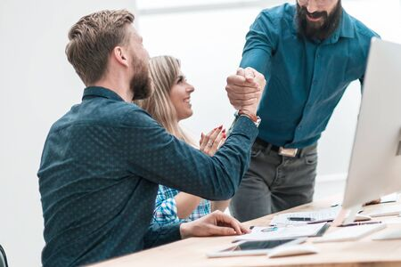 happy employees supporting each other with their handshake