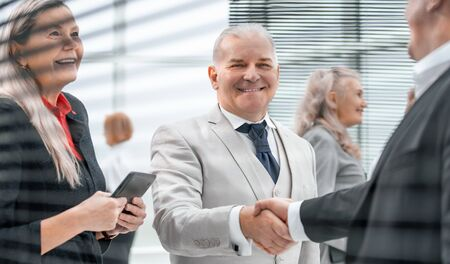 확대. 웃고 있는 사업가들은 악수로 서로 인사합니다.