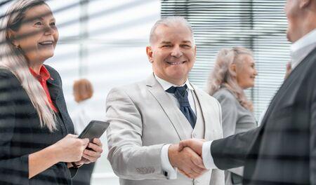 de cerca. Los empresarios sonrientes se saludan con un apretón de manos.