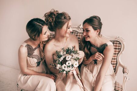 cheerful bride with her girlfriends sitting together