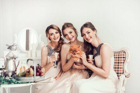 happy girls and the bride sitting in the boudoir Foto de archivo
