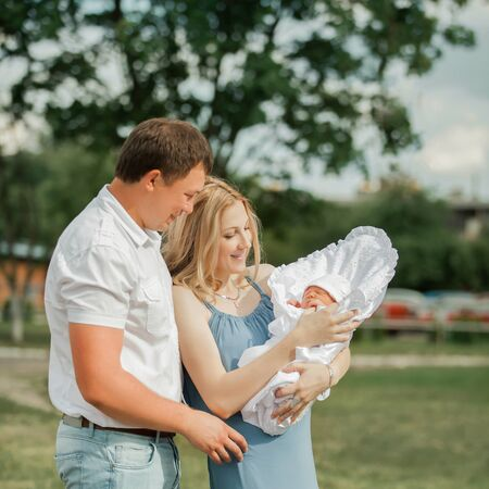 portrait of a happy married couple with their newborn baby.